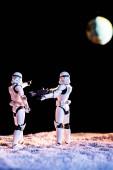 Kyjev, Ukrajina-25. května 2019: bílý císařský Stormtrooper s pistolí na černém pozadí s planetou země