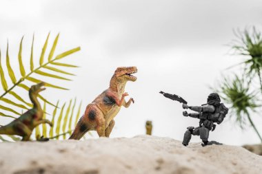 Selective focus of plastic toy soldier aiming with gun at toy dinosaur on sand dune with tropical leaves stock vector