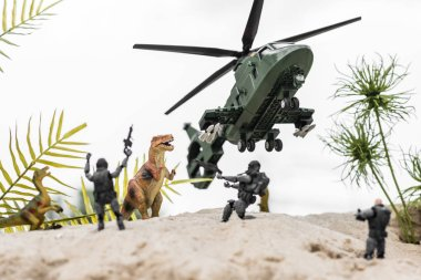 Selective focus of plastic soldiers aiming at toy dinosaurs on sand dune with helicopter in sky stock vector
