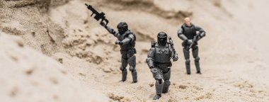 Selective focus of plastic toy soldiers on sand dune with guns, panoramic shot stock vector