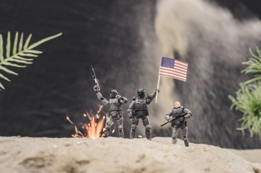 Selective focus of toy soldiers with guns and american flag standing near explosion on sand dune stock vector