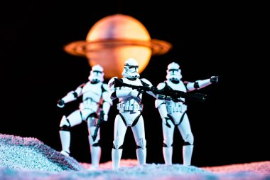 KYIV, UKRAINE - MAY 25, 2019: white imperial stormtroopers with guns on cosmic planet isolated on black stock vector