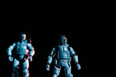 Selective focus of toy plastic soldiers isolated on black stock vector