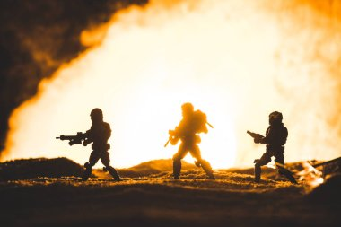 Silhouettes of toy soldiers with guns walking on planet with sun in smoke on background stock vector