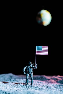 Toy soldier holding national american flag in space with planet Earth on black background stock vector