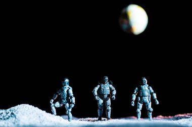 Toy soldiers standing on planet in space on black background with planet earth stock vector