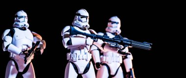 KYIV, UKRAINE - MAY 25, 2019: panoramic shot of white imperial stormtroopers with guns isolated on black stock vector