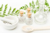 glass bottles with small pills near mortar and pestle, wooden spoon, jar and green leaves on white