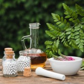 selective focus of pestle near mortar with flowers, glass bottles and jug with oil on wooden table