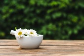 pestle in mortar with chrysanthemum flowers on wooden table