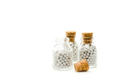glass bottles with round small pills and wooden corks isolated on white