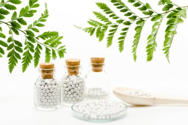selective focus of small pills in glass bottles with wooden corks near spoon and green leaves on white