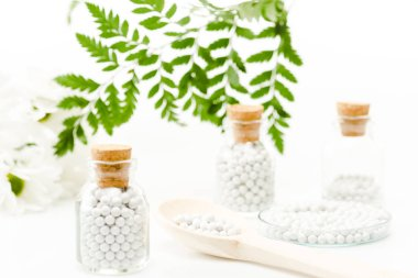 selective focus of pills in glass bottles with wooden corks near green leaves on white