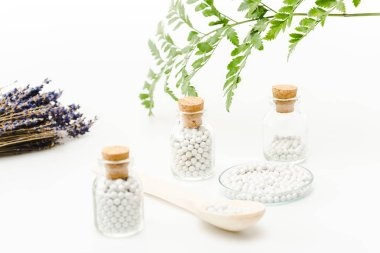 selective focus of medicine in glass bottles with wooden corks near green leaves on white