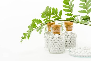 Selective focus of medicine in glass bottles with wooden corks and green leaves on white stock vector