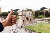ROME, ITALY - JUNE 28, 2019: partial view of man showing thumb up in front of arch of constantine