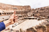 ROME, ITALY - JUNE 28, 2019: partial view of man showing thumb up in front of Colosseum