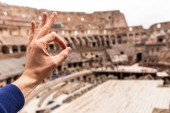 ROME, ITALY - JUNE 28, 2019: cropped view of man showing okay sign in front of Colosseum