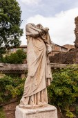 ROME, ITALY - JUNE 28, 2019: ancient headless statue under blue sky