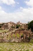 rom, italien - 28. juni 2019: touristen in der nähe antiker gebäude am römischen forum unter blauem himmel