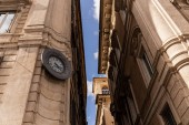 ROME, ITALY - JUNE 28, 2019: bottom view of buildings with street clock in rome, italy