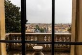 Fotografia vecchio balcone di cemento dietro la finestra a Roma, Italia