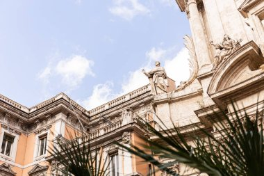 ROME, ITALY - JUNE 28, 2019: selective focus of green plants and old building with statues in rome, italy stock vector