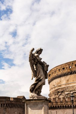 ROME, ITALY - JUNE 28, 2019: ancient roman statue near old building in sunny day under blue sky
