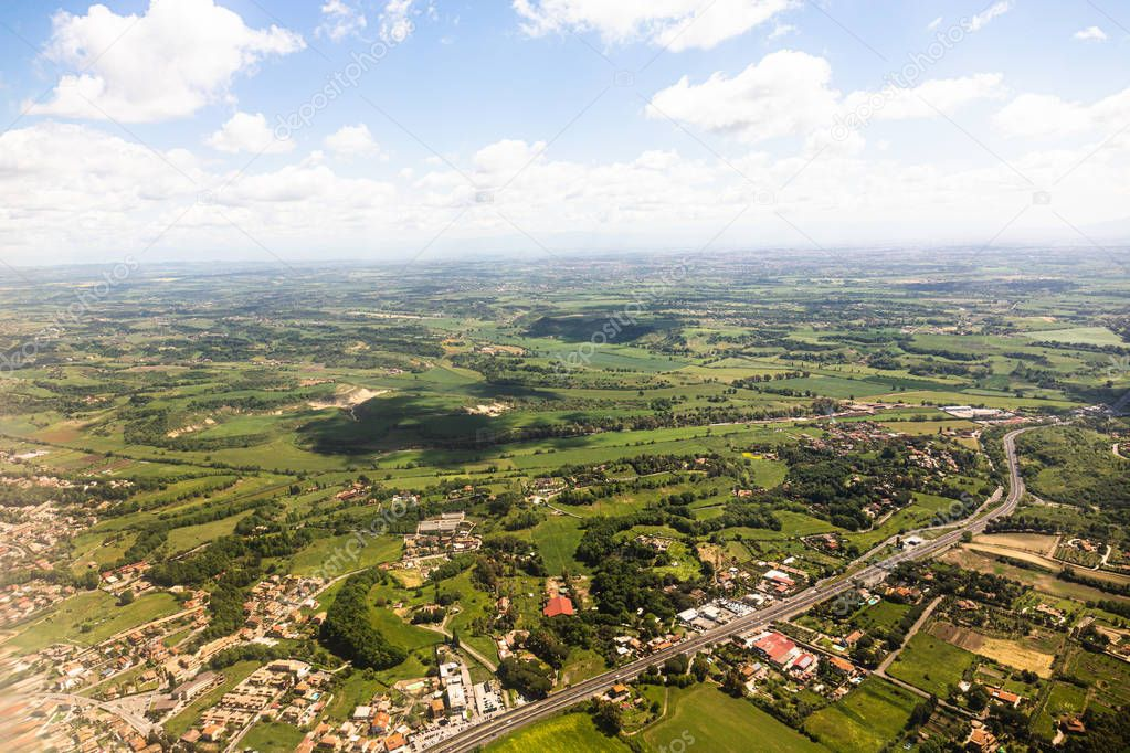 aerial view of beautiful green landscape with hills and houses under blue sky in rome, italy