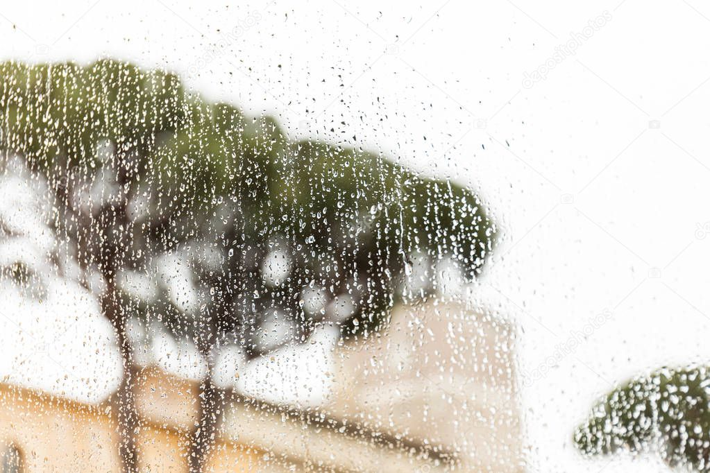 window glass with rain drops in rome, italy