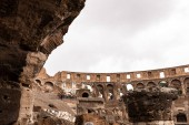 ROME, ITALY - JUNE 28, 2019: ruins of colosseum and tourists under grey sky