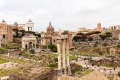 Řím, Itálie-28. červen 2019: turisté, kteří chodí po římském fóru pod šedou oblohou