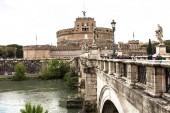 Řím, Itálie-28. června 2019: řeka Tiber a lidé na starém mostě pod zamračený oblohou