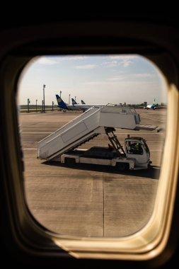 ROME, ITALY - JUNE 28, 2019: airplanes and ground support equipment behind plane window in rome, italy stock vector