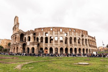 ROME, ITALY - JUNE 28, 2019: colosseum and crowd of tourists under grey sky stock vector
