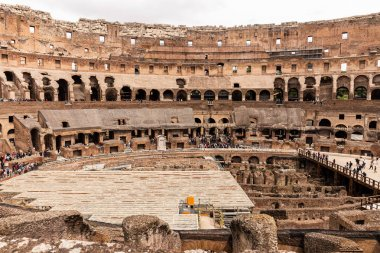 ROME, ITALY - JUNE 28, 2019: ruins of colosseum and crowd of tourists under grey sky stock vector