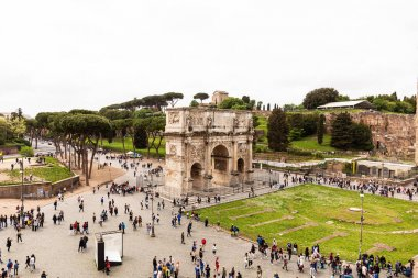 ROME, ITALY - JUNE 28, 2019: crowd of tourists in square near arch of Constantine under grey sky stock vector