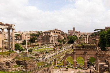 ROME, ITALY - JUNE 28, 2019: tourists walking around roman forum under grey sky stock vector