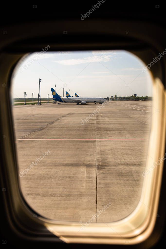 ROME, ITALY - JUNE 28, 2019: airplanes at aerodrome behind plane window in rome, italy