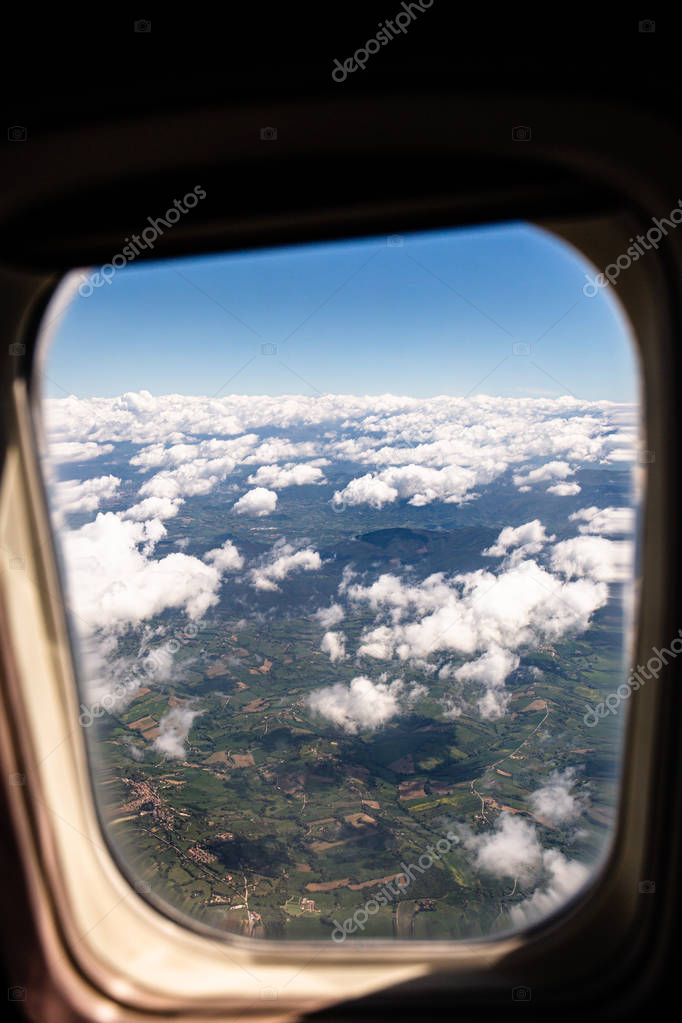aerial view of land under clouds from plane window, rome, italy