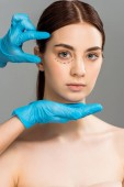 cropped view of plastic surgeon in latex gloves near attractive woman with marks on face isolated on grey