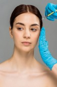 cropped view of plastic surgeon making beauty injection to attractive naked woman isolated on grey