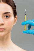cropped view of plastic surgeon holding syringe near naked woman isolated on grey