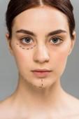 komoly fiatal nő a jelek az arcon izolált szürke