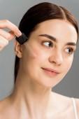 allegra donna bruna tenendo pipetta durante lapplicazione di siero sul viso isolato sul grigio