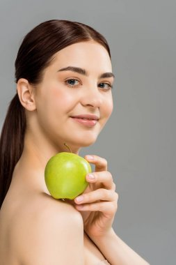 Brunette nude woman holding green apple on shoulder isolated on grey stock vector