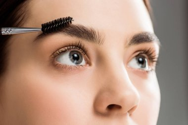 cropped view of young woman styling eyebrow with eyebrow brush on grey