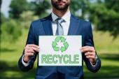 oříznutý pohled na mladou podnikatele držící kartu s nápisem recyklace při stání v parku
