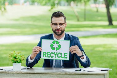 Young businessman sitting at table with plant, smartphone and notebooks in park, holding card with recycle inscription and looking at camera stock vector