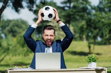 young businessman sitting at table with laptop, flowerpot and glasses, smiling and holding football over head